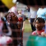 Jada Moore, an 8-year-old from Nashville, Georgia and Jara Hallback, a 5-year-old from Nashville, Georgia, take a break from riding rides and enjoy candy apples at the Georgia National Fair on Saturday, October 10, 2015. (Photo/Casey Lemmings, cklemm@uga.edu)
