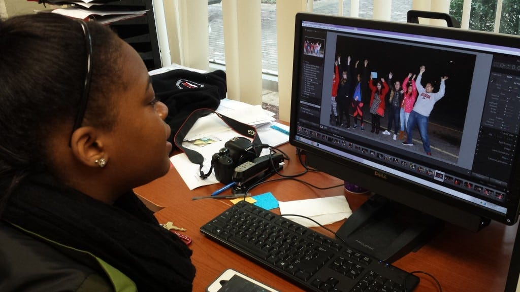 Juanne-Dae Thomas, historian for the Residence Hall Association (RHA) for the University of Georgia sits at computer in the RHA boardroom, editing photos taken at the Roll Bounce event hosted a week prior in Athens, Georgia, on Tuesday, Feb. 23, 2016. (Photo/ Precious D. Davis