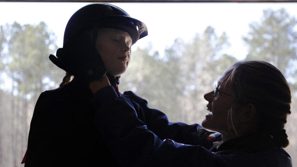 Marjolein Geven, 44, a dressage instructor and horse trainer from Eindhoven, Netherlands, adjusts the helmet of her daughter, Tessa, before competition in Hamilton, Georgia, on Saturday, February 27, 2016. Geven coached Tessa in the youth dressage competition at the Poplar Place Farm schooling show over the weekend. (Photo/Ansley Walker, eawalker@uga.edu) Geven: 706-570-2323