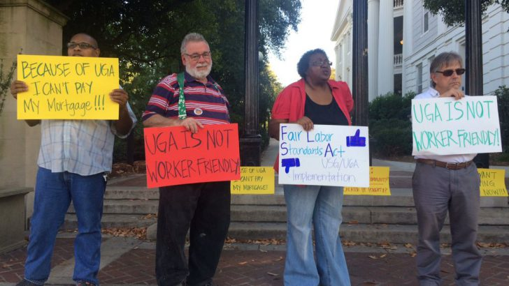 Employees stand outside UGA Arch to protest