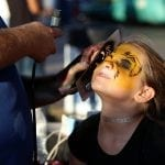 Chloe Rowell, 8, from Macon, Georgia, sits as she gets her face painted to look like a tiger at the Georgia National Fair in Perry, Georgia on October 8, 2016. The Georgia National Fair takes place from October 6-16 and happens once a year. (Photo/Katelyn Umholtz, kumholtz@uga.edu)