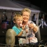 Luke Comeau, 5, from Toccoa, engulfs with great power a mere piece of cotton candy while sitting in his grand aunt's lap, June Stubb, 73,  who resides in Perry, Georgia, at the Georgia National Fair in Perry, Georgia, on October 8, 2016. (Photo/Henry Taylor/henrytaylorphoto@gmail.com)