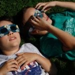 Sam Harrell and Oscar Justus lay on their backs to get a better view of the eclipse during the eclipse viewing party at Chase Street Elementary School in Athens, Georgia, on Monday, August 21, 2017. (Photo/Grason Passmore)