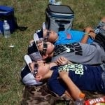 "Brant Brown (back), 7, a student at Elbert County Elementary, looks up at the solar eclipse with his friends, Evan Rorick (middle), 10, a student at Elbert County Elementary, and Rylan Brown (front), 9, a student at Elbert County Elementary at the eclipse viewing at Lake Hartwell, in Hartwell, Georgia, on Monday, August 21, 2017. The boys all agreed that the eclipse was ""the coolest"". (Photo/Nicole M. Adamson)"