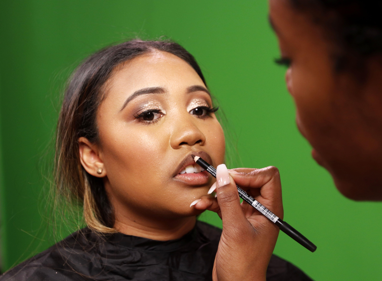 Johnna Young, a local makeup artist, applies lipstick to reporter Enya Spicer's lips.