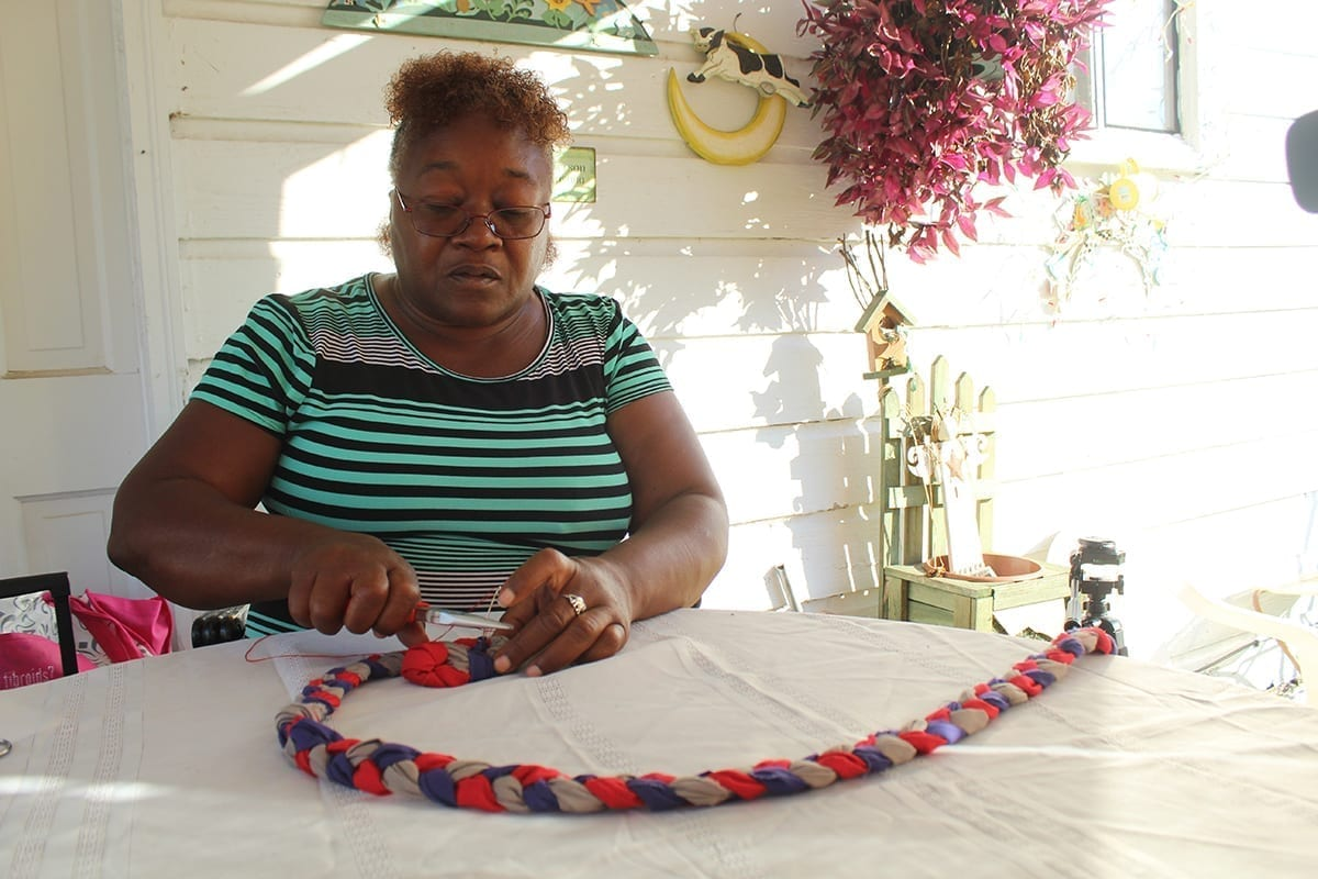 """Zelma Griffith begins constructing a new rag rug on Oct. 3, 2018 at her home in Athens, Ga. Griffith has always been interested in crafting and has created several different products before focusing on rag rugs. """"I come up with these ideas, I think about it, I study it out in my mind whether it's me sketching something on paper or even just making it by hand. I study it first in my mind and then I go to creating it, whether it's on paper or either by hand. I got a lot of stuff that I created before Greg gave me this idea. I just got stuff,"""" said Griffth. (Photo by Danielle Bartling)"""