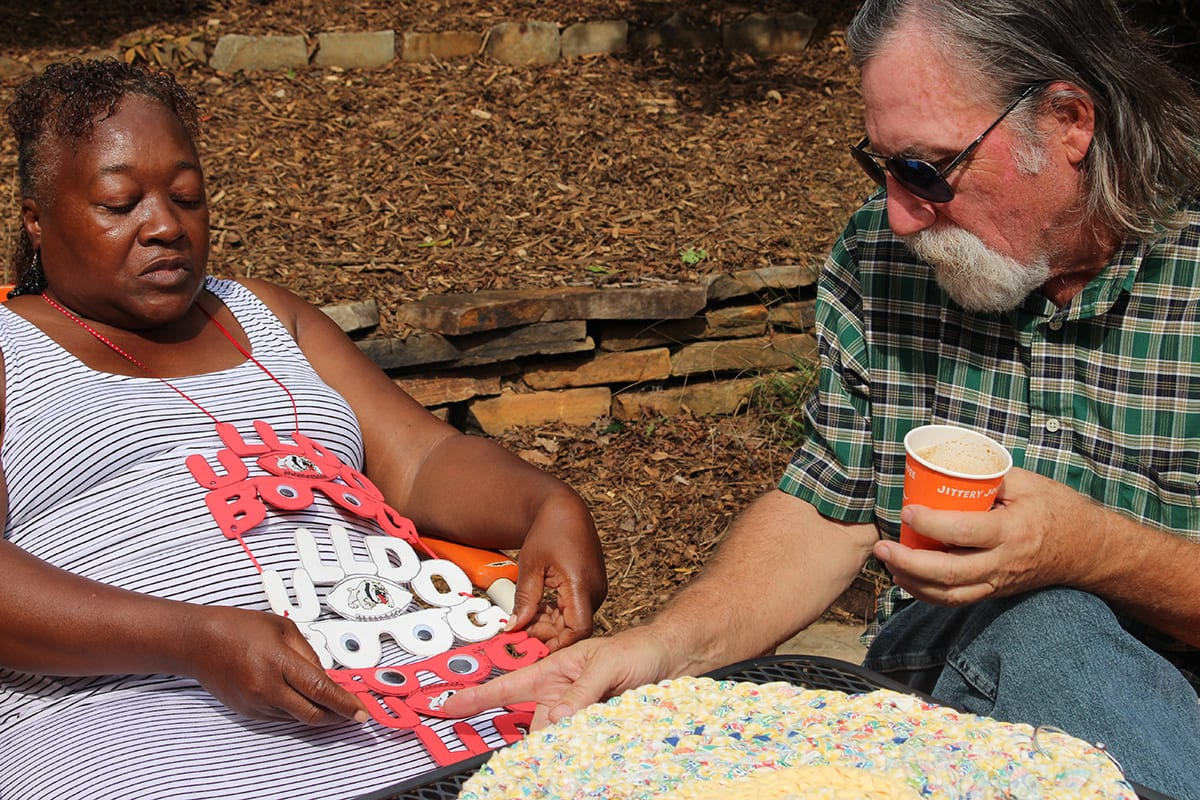 "Zelma Griffith and Greg Wagstaff discuss Griffith's rag rugs and her other crafts at Jittery Joe's on Baxter Street in Athens, Ga. on Sept. 28, 2018. Wagstaff gave Griffith the idea to start making rag rugs. ""I'm gonna tell you about my friend right here, he the one who got me hooked on making these. He told me about the idea. He really pretty much just throw'd it out the air. But I didn't know what I was doing at first,"" Griffith stated. (Photo by Kristen Adaway)"