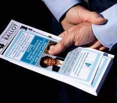 """Jim Ford, 74, from Pasadena, Maryland, holds flyers for Stacey Abrams and Deborah Gonzalez in Athens, Georgia, on Saturday, November 3, 2018. Ford is currently retired but previously worked at the University of Georgia conducting research on military families. """"I'm not retired. I'm taking a year off,"""" Ford said. (Photo/Whitley Carpenter, wcc53060@uga.edu)"""