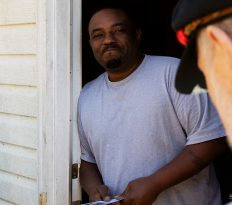 """Corey Griffin, 41, from Miami, Florida, talks to Jim Ford in Athens, Georgia, on Saturday, November 3, 2018. Griffin works as a driver's helper for UPS, and he hasn't decided how to vote. """"I'll have to see how it goes. One side wants to balance the checkbook, and the other side wants to reduce crime,"""" Griffin said. (Photo/Whitley Carpenter, wcc53060@uga.edu)"""