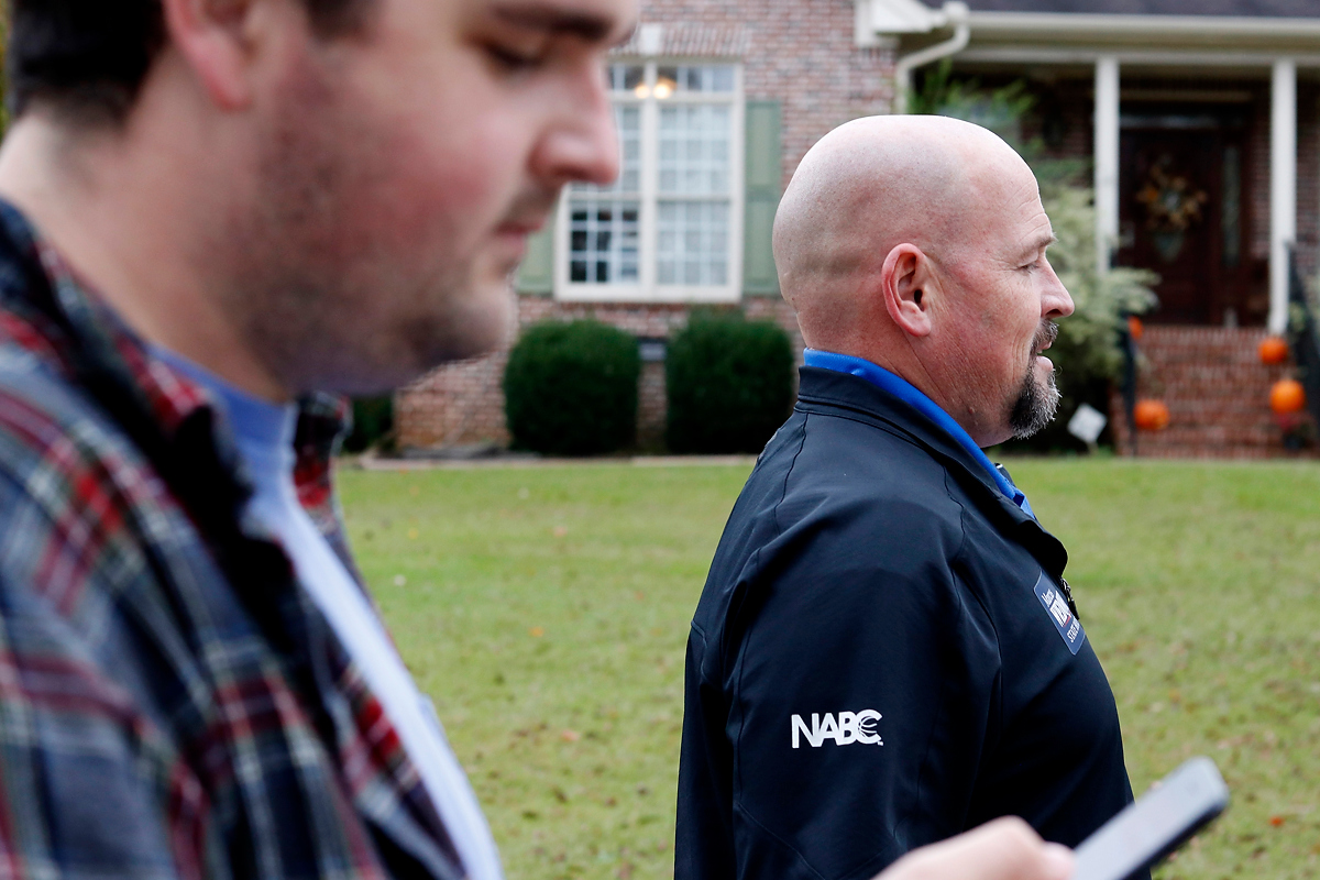 Justin Strength looks to see where the next house is while walking alongside Marcus Wiedower on Friday, November 2, 2018 in Watkinsville, Georgia. Wiedower is the Republican candidate running for State House in Georgia House district 119. (Emily Graven, emilyrgraven@gmail.com)