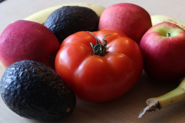 A tomato, two avocados, three apples and two bananas sit on a table.