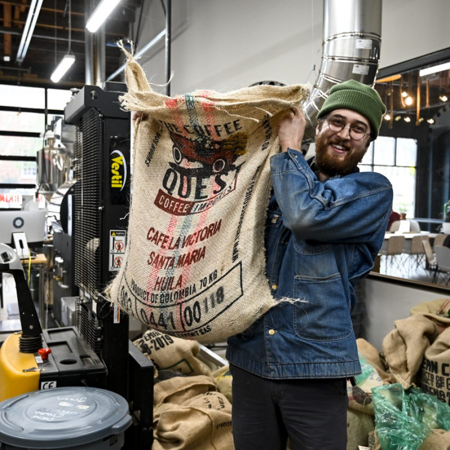 Director of coffee Ben Bowdoin poses with a bag of green, unroasted coffee at 1000 Faces on Wednesday, Feb. 5, 2020 in Athens, Georgia. (Photo/Taylor Gerlach)