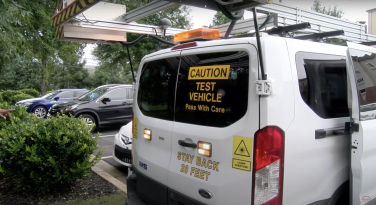 A white van equipped with lasers and flashing lights.