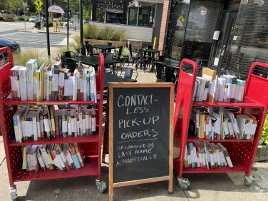 Two red carts loaded with books sit behind a chalkboard sign.