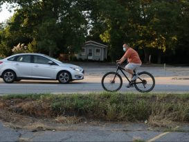 man rides bike on road with car in background