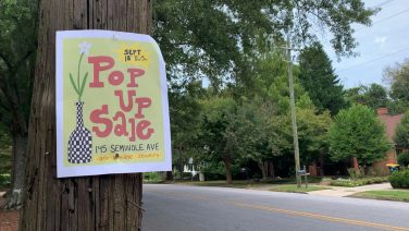 """A paper sign that reads """"Pop Up Sale"""" hangs on a wooden telephone pole next to an empty street"""